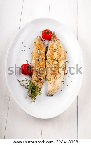 grilled mackerel with thyme and tomato on a white plate