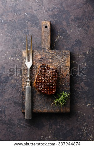 Grilled marbled meat Steak with rosemary and meat fork on meat cutting board on dark background - stock photo