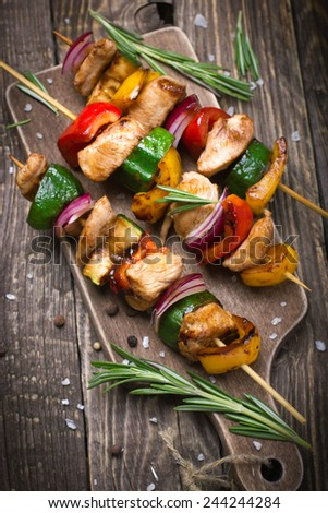 Grilled meat and vegetable kebabs on wooden cutting board - stock photo