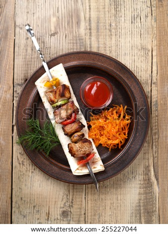 Grilled meat and vegetable kebabs with sauce, selective focus - stock photo