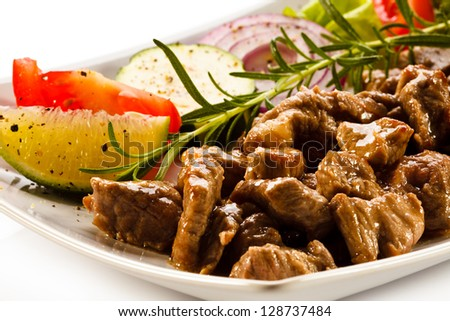 Grilled meat and vegetables on white background - stock photo
