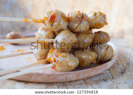 Grilled meat ball with sweet spicy sauce on wood dish. Selective focus