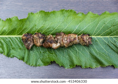 Grilled meat, barbecue, cooked on a skewer in a strong fire. A food dish made from beef or pork, served on a green leaf. Sheet wasabi for serving sushi or fish - stock photo