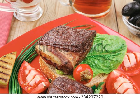 grilled meat : beef ( lamb ) garnished with vegetables , juice and olives on red plate over wooden table - stock photo