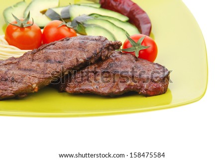 grilled meat beef steak with pasta avocado and tomatoes on green plate isolated over white background