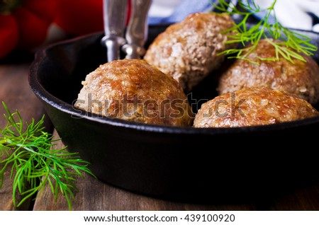 Grilled meat cutlets in a frying pan on a wooden background. Selective focus. - stock photo