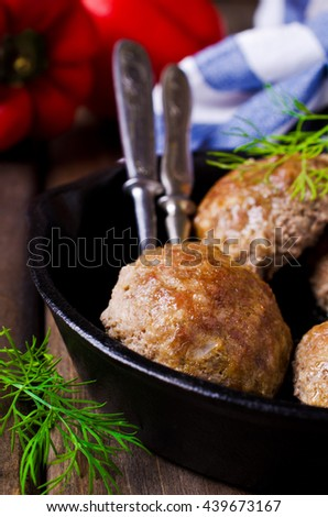 Grilled meat cutlets in a frying pan on a wooden background. Selective focus.