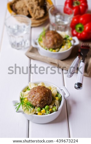 Grilled meat cutlets with pasta and vegetables on a wooden background. Selective focus. - stock photo