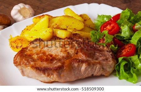 grilled meat fillet steak with fried potato and vegetables salad in a plate on wooden table