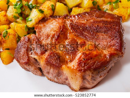 grilled meat fillet steak with fried potato in a plate on wooden table