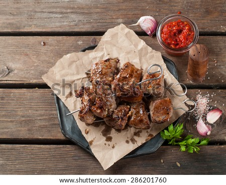 Grilled meat (kebab) with sauce on wooden background, selective focus - stock photo