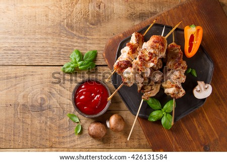 Grilled meat (kebab) with vegetables and  sauce on wooden background, selective focus