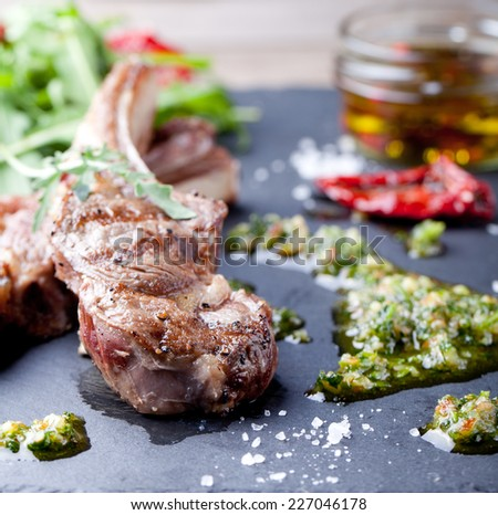 Grilled meat, mutton, lamb rack with fresh salad and sauce on black slate stone plate.  - stock photo
