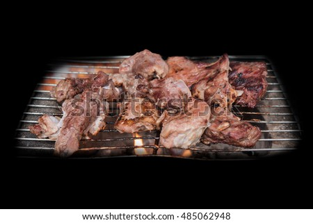 Grilled meat on a charcoal grill isolate on black,fresh beef,selective focus