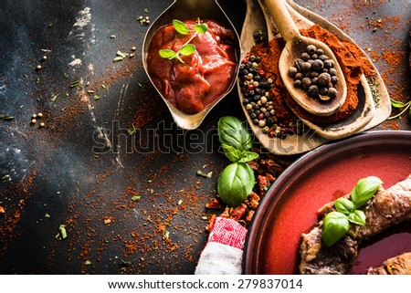 grilled meat on a plate with tomato sauce, spices on textured black background - stock photo