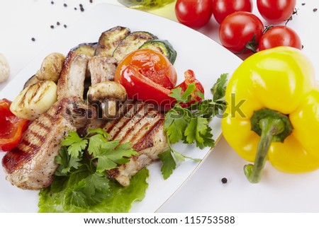 Grilled meat on white plate with vegetables