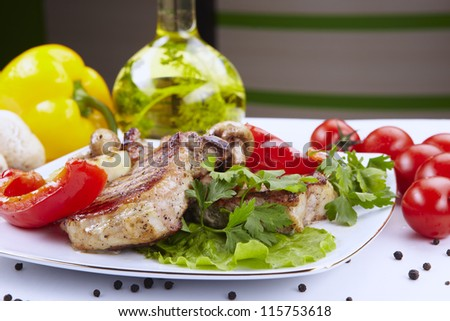 Grilled meat on white plate with vegetables - stock photo
