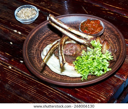 Grilled meat ribs. Served with sauce, greens on a pita in a ceramic plate. - stock photo