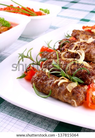 Grilled meat rolls with giant white beans and sauce, close up - stock photo
