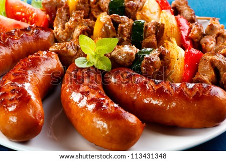 Grilled meat, sausages and vegetables - stock photo