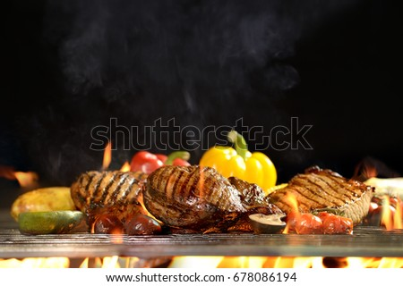 Grilled meat /steak with vegetable on the flaming grill