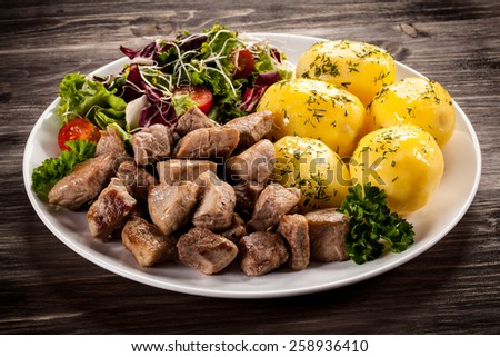 Grilled meat with boiled potatoes and vegetables - stock photo