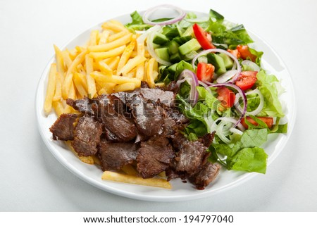 Grilled meat with fried potatoes and vegetable salad - stock photo