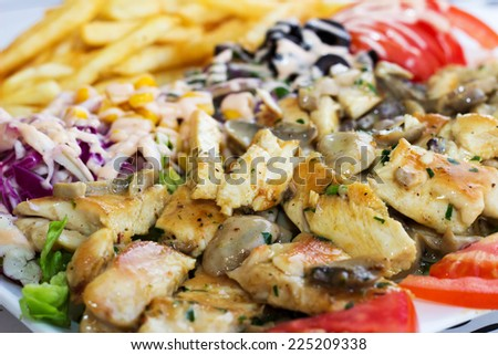 Grilled meat with mushrooms served with vegetables and fries.