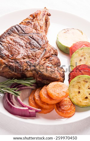 Grilled meat with vegetables and rosemary on the plate