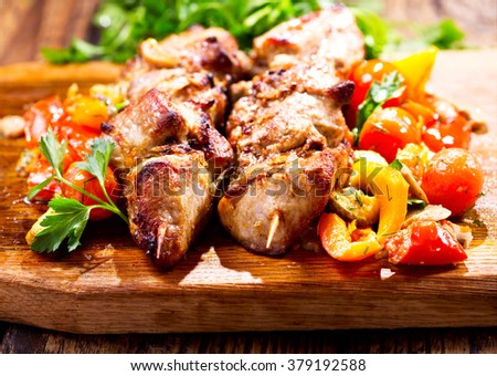 grilled meat with vegetables on wooden board