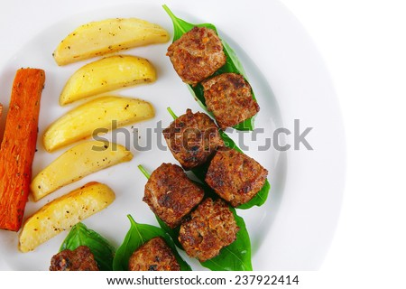 grilled meatballs on white plate with basil and potatoes - stock photo