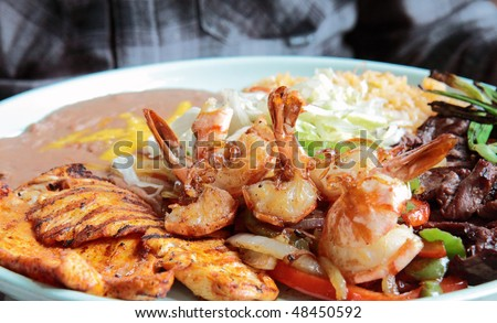 Grilled Mexican platter of shrimp, chicken, and beef - stock photo