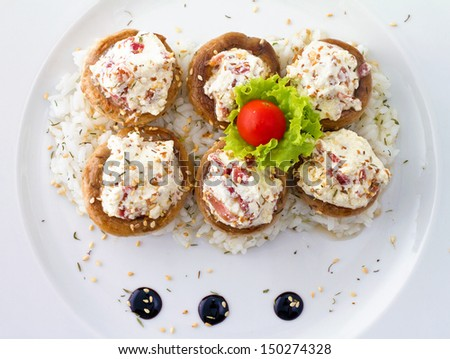 Grilled mushrooms stuffed with cream cheese and prosciutto and served over rice - stock photo