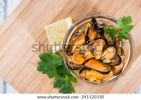 Grilled Mussels pickled in oil with different fresh herbs - stock photo