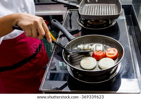 grilled onion and tomato in frying pan