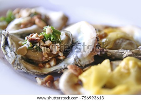 Grilled Oyster with cheese, fried peanut and sliced scallion leafs