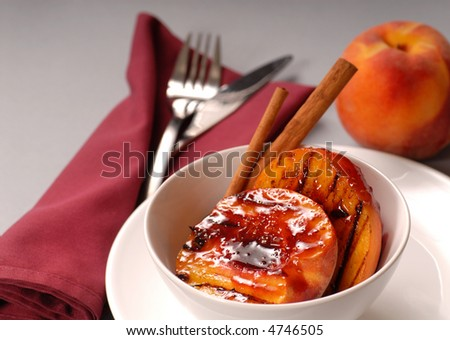 Grilled peaches with raspberry sauce, cinnamon sticks with a peach in the background - stock photo