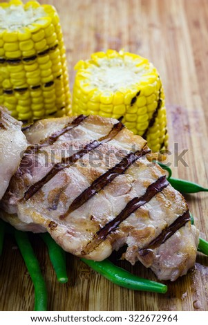 Grilled piece of pork with green beans and corn cobs, on wooden chopping board. - stock photo