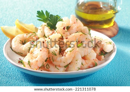 Grilled pink shrimps seasoned with fresh herbs and drizzled with olive oil served in a dish with lemon as a delicious seafood delicacy, on a textured blue table - stock photo