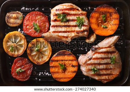 Grilled pork and autumn vegetables on a grill pan. top view horizontal macro