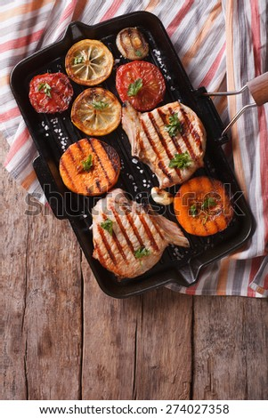 Grilled pork and pumpkin on a grill pan. Vertical view from above - stock photo