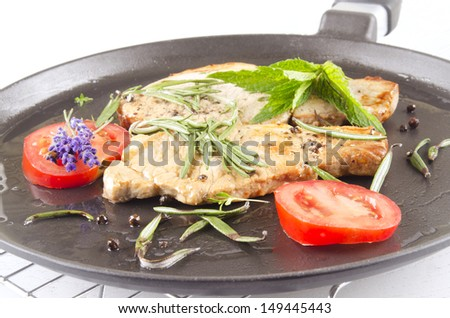 grilled pork chop in a pan with herbs