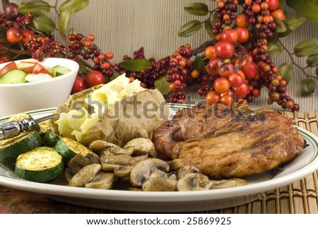 Grilled pork chop platter with seasoned zucchini mushrooms and baked potato with side salad copy space