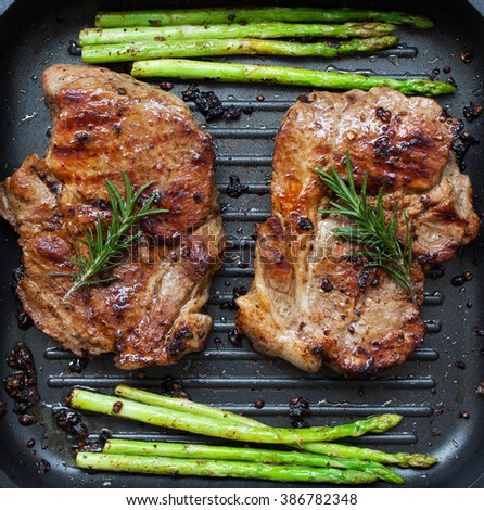 grilled pork chop with asparagus and rosemary  in pan - stock photo