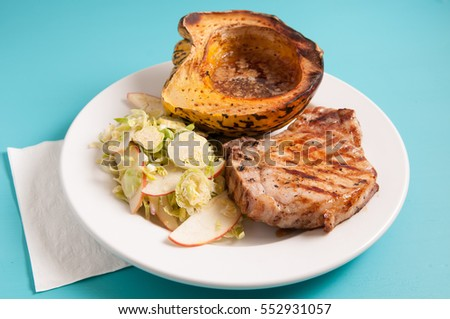 grilled pork chop with brussel sprout salad and squash