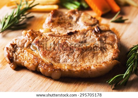 grilled pork chop with vegetable and french fries on wooden board - stock photo