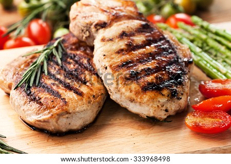 grilled pork chop with vegetable on wooden board - stock photo