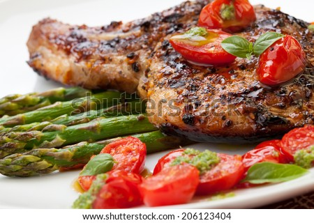 Grilled pork chops and asparagus. Served with fried grape tomatoes salad and pesto sauce.  - stock photo