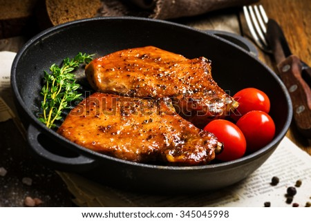 Grilled pork chops in sweet honey glaze, served in grill iron skillet with fresh thyme, rye bread and cherry tomatoes, close up. Selective focus - stock photo