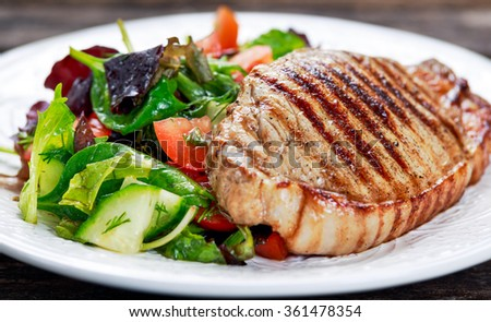 Grilled pork meat and vegetables on plate. - stock photo